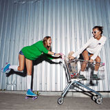 Two beautiful young girls with a skateboard, roller skates and a Royalty Free Stock Photography