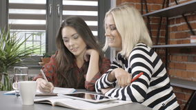 Two beautiful young girls studying at modern loft apartment. stock video footage