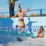 Two beautiful young girls in sunglasses in an empty pool Stock Images