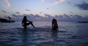 V10780 Two 2 beautiful young girls at sunset sunrise splashing on the beach in evening with water and sand Stock Photo