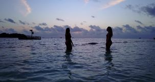 V10777 Two 2 beautiful young girls at sunset sunrise splashing on the beach in evening with water and sand Royalty Free Stock Images