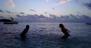 V10781 Two 2 beautiful young girls at sunset sunrise splashing on the beach in evening with water and sand Stock Photos