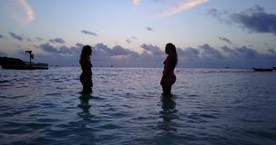 V10778 Two 2 beautiful young girls at sunset sunrise splashing on the beach in evening with water and sand Stock Photo