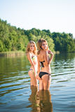 Two beautiful young girls in swimsuits  lake Stock Photo