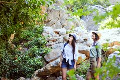 Two beautiful young girls travel in the mountains and enjoy the view of the landscape of green trees. Royalty Free Stock Images