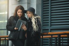 Two beautiful young girls in warm clothes discussing work on a tablet. On the street near the building Stock Photos