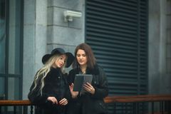 Two beautiful young girls in warm clothes discussing work on a tablet. On the street near the building Stock Image