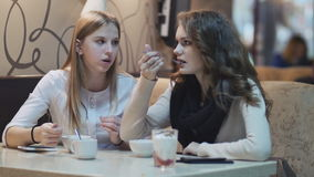 Two beautiful young girls in white blouses, sitting at a table in  cafe, eating and talking. Two beautiful young girls in white blouses, sitting at a table in a stock footage