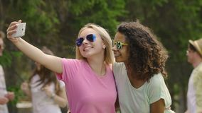 Two beautiful young ladies dancing, laughing and posing for selfie on smartphone. Stock footage stock video footage