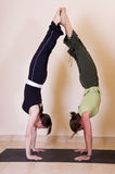 Two beautiful young ladies doing yoga. Two beautiful young ladies doing back to back handstands, showing perfect control, flexibility and fitness stock images