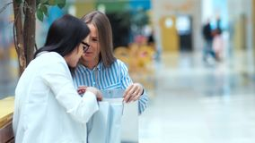Two beautiful young ladies having rest and discussing something after shopping in the mall. Two beautiful young ladies having rest and discussing something stock video