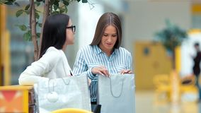 Two beautiful young ladies having rest and discussing something after shopping in the mall.  stock video footage