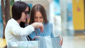 Two beautiful young ladies having rest and discussing something after shopping in the mall. Two beautiful young ladies having rest and discussing something stock video footage