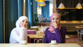 Two beautiful young Muslim women laughing and joking while sitting at a table in a cafe stock video