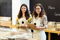 Two beautiful young saleswomen looking at camera while doing inventory in organic store. Royalty Free Stock Photo