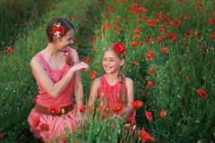 Two beautiful young sisters walking in poppy field Stock Image