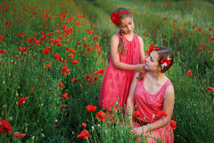 Two beautiful young sisters walking in poppy field Royalty Free Stock Photography