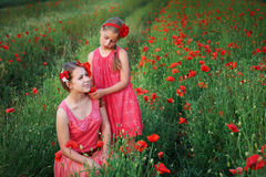 Two beautiful young sisters walking in poppy field Stock Images
