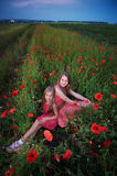 Two beautiful young sisters walking in poppy field Stock Photography