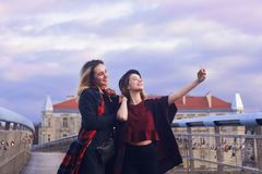 Two beautiful young student girlfriends having fun making funny faces and taking self portraits with smart-phone. friendship. Trav Royalty Free Stock Photos