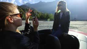 Two beautiful young stylish girls take photos on a smartphone inside a red convertible. Funny photo shoot on vacation