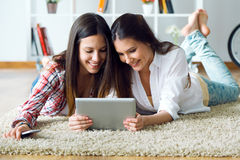 Two beautiful young woman friends using digital tablet at home. Stock Image