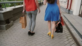 Two beautiful young woman friends walking with shopping bags, talking having fun, back view, slow mo stedicam shot. Two beautiful young woman friends in colorful stock footage