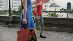 Two beautiful young woman friends walking with shopping bags, talking having fun, side view, slow mo stedicam shot stock video