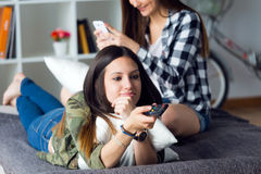 Two beautiful young woman staying on sofa at home. Stock Image