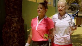 Two beautiful young woman tennis players chatting. As they walk along a wall at the club passing under the shade of a tree stock video footage