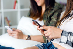 Two beautiful young woman using mobile phone at home. Royalty Free Stock Photos