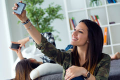 Two beautiful young woman using mobile phone at home. Royalty Free Stock Image
