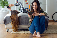Two beautiful young woman using mobile phone at home. Stock Photography