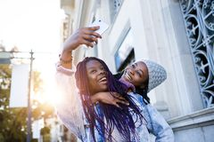 Two beautiful young woman using mobile phone in the street. stock images