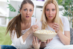 Two Beautiful young woman watching TV and eating popcorn. Young women watching scary movie at home Royalty Free Stock Photos