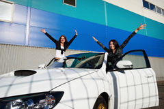 Two beautiful young woman and white sports car Stock Photo