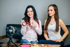 Two young womans reviewing beauty products on video blog at home. Two Beautiful young womans reviewing beauty products on video blog at home Royalty Free Stock Photos