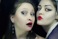 Two beautiful young women. With bright make-up on black background stock photo