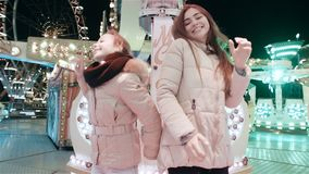 Two beautiful young women actively dance amid amusement rides in an amusement park. Mom and daughter are having fun in the lunapark stock footage