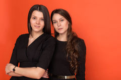 Two beautiful young women in business suits on a red background Royalty Free Stock Photos
