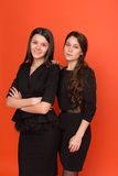 Two beautiful young women in business suits on a red background Royalty Free Stock Images