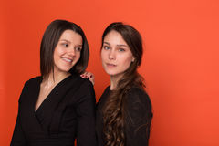 Two beautiful young women in business suits on a red background Stock Images