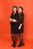 Two beautiful young women in business suits on a red background Stock Photography