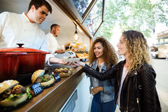 Two beautiful young women buying meatballs on a food truck. Portrait of two beautiful young women buying meatballs on a food truck in the park Royalty Free Stock Photography