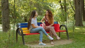 Two beautiful young women chatting in the park. 4k stock video