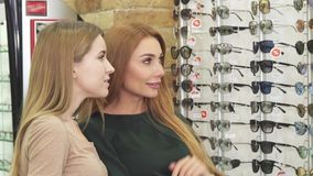 Two beautiful young women choosing eyewear in optician store stock video footage