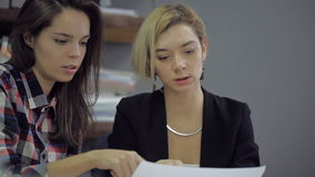 Two beautiful young women considering and discussing something on the sheets of paper. One of them has dark long hair, wearing a plaid shirt, the second has a stock footage