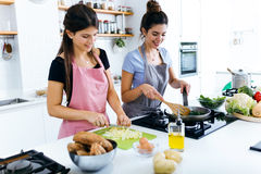 Two beautiful young women cooking chards and slicing potatoes in the kitchen. Stock Photo