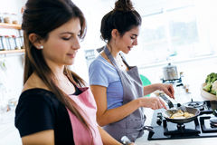 Two beautiful young women cooking chicken breast in the pan. Royalty Free Stock Photos