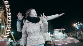 Two beautiful young women dance at night in the park of attaractions on the background of a glowing Ferris wheel. Active movement in the dance of beautiful stock video footage